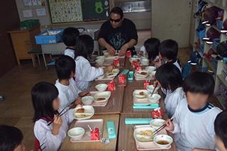 佐藤尋宣と給食を食べる小学生